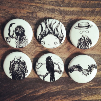 Buttons featuring my drawings made by nerdbiskit. Photo appears on nerdbiskit.tumblr.com